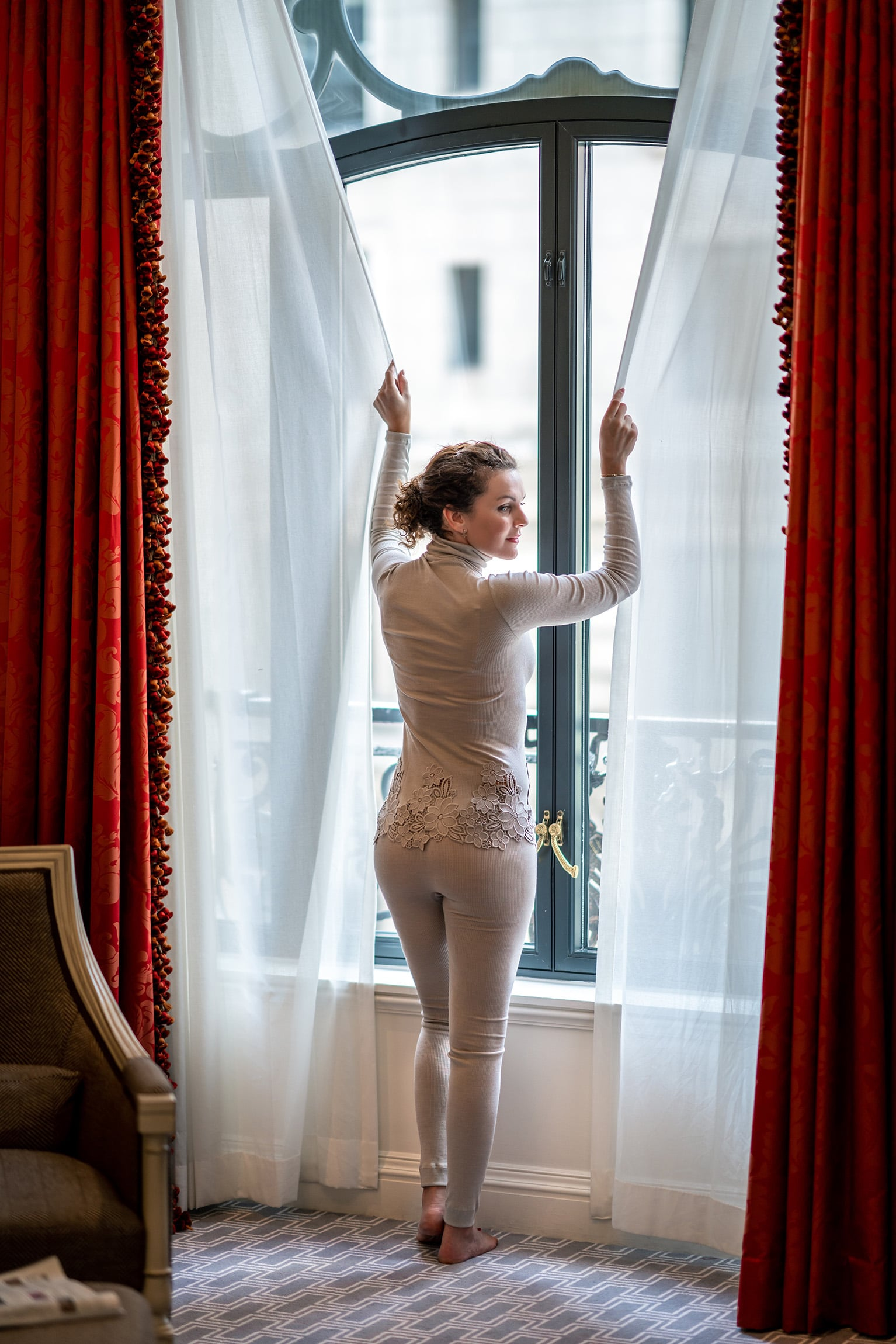 Woman wearing Zimmerli and closing curtains at St Regis New York