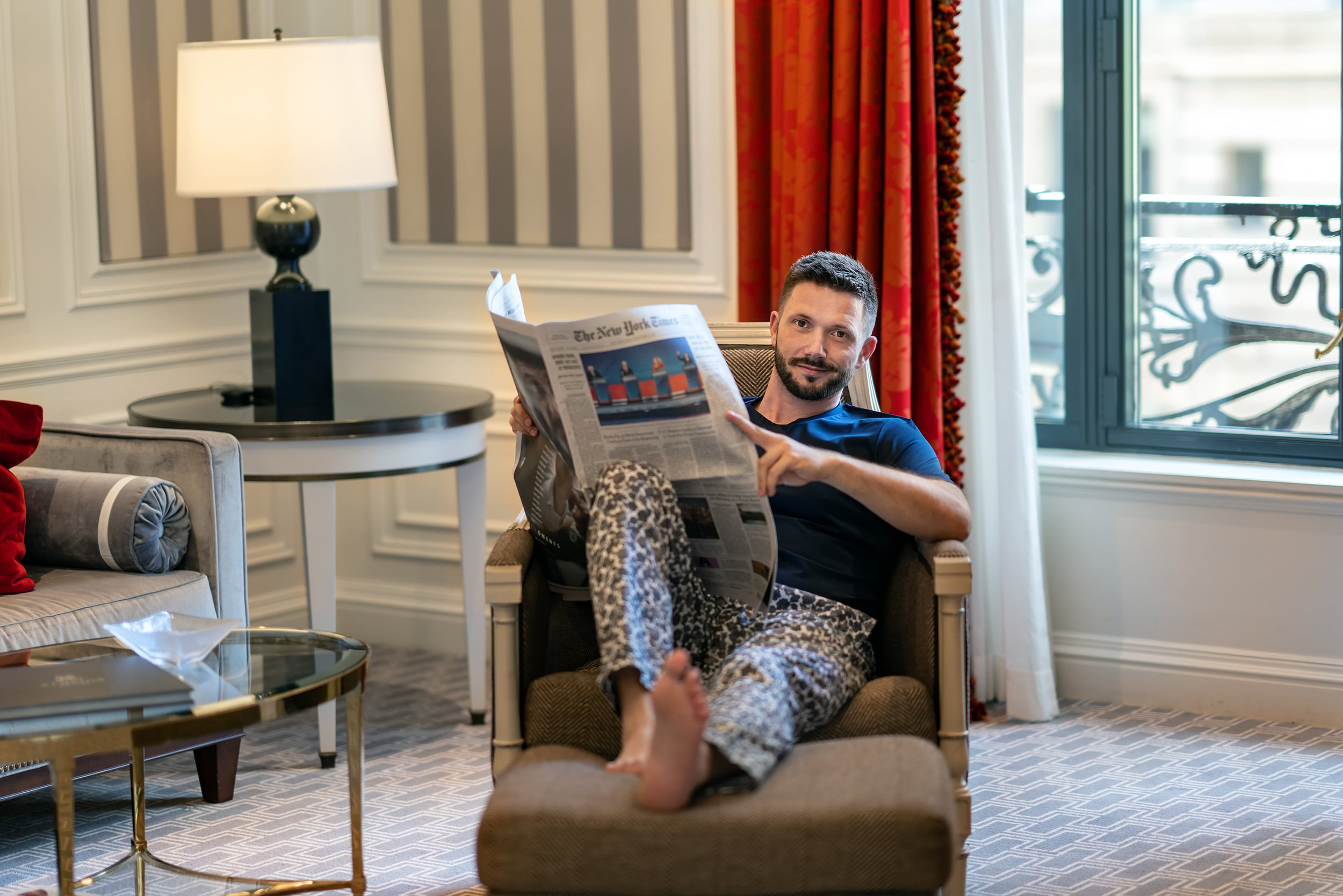 Man reading newspaper in the Grand Suite at The St Regis New York