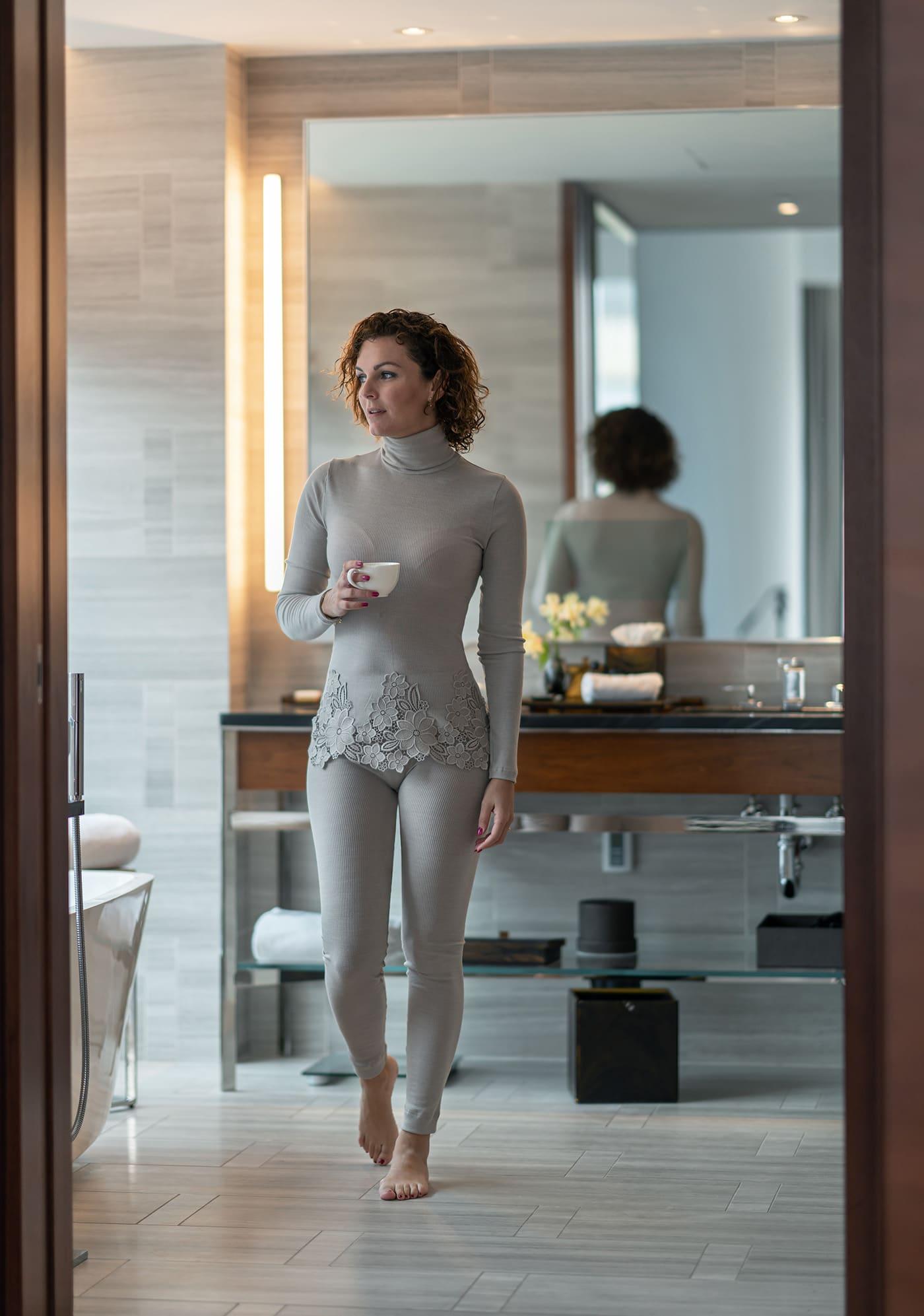 Woman with coffee in bathroom in Park Hyatt New York