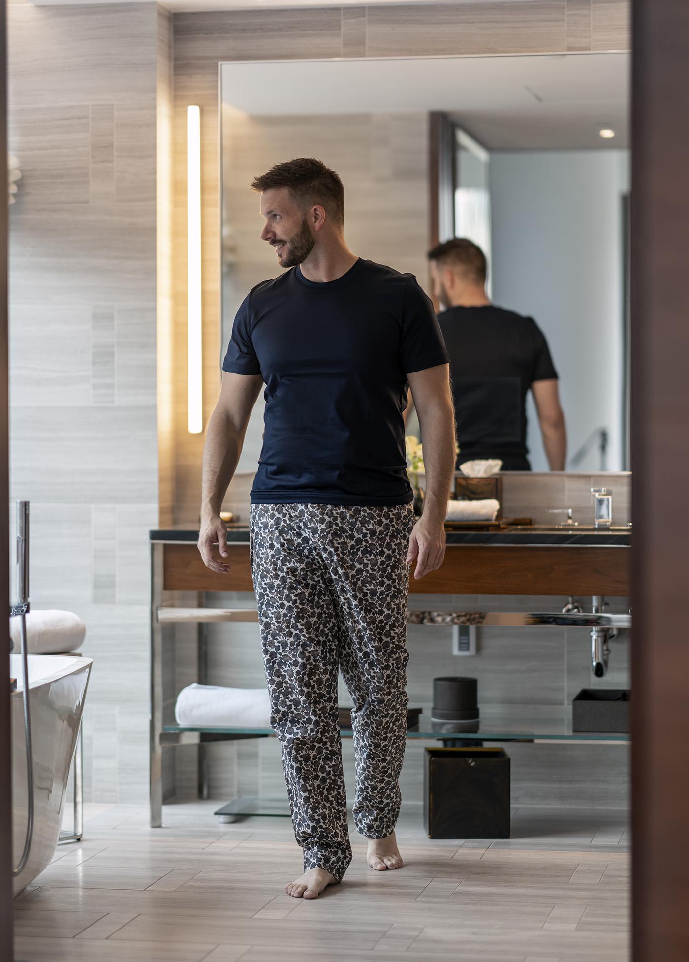 Man in pyjamas in bathroom of suite in Park Hyatt New York