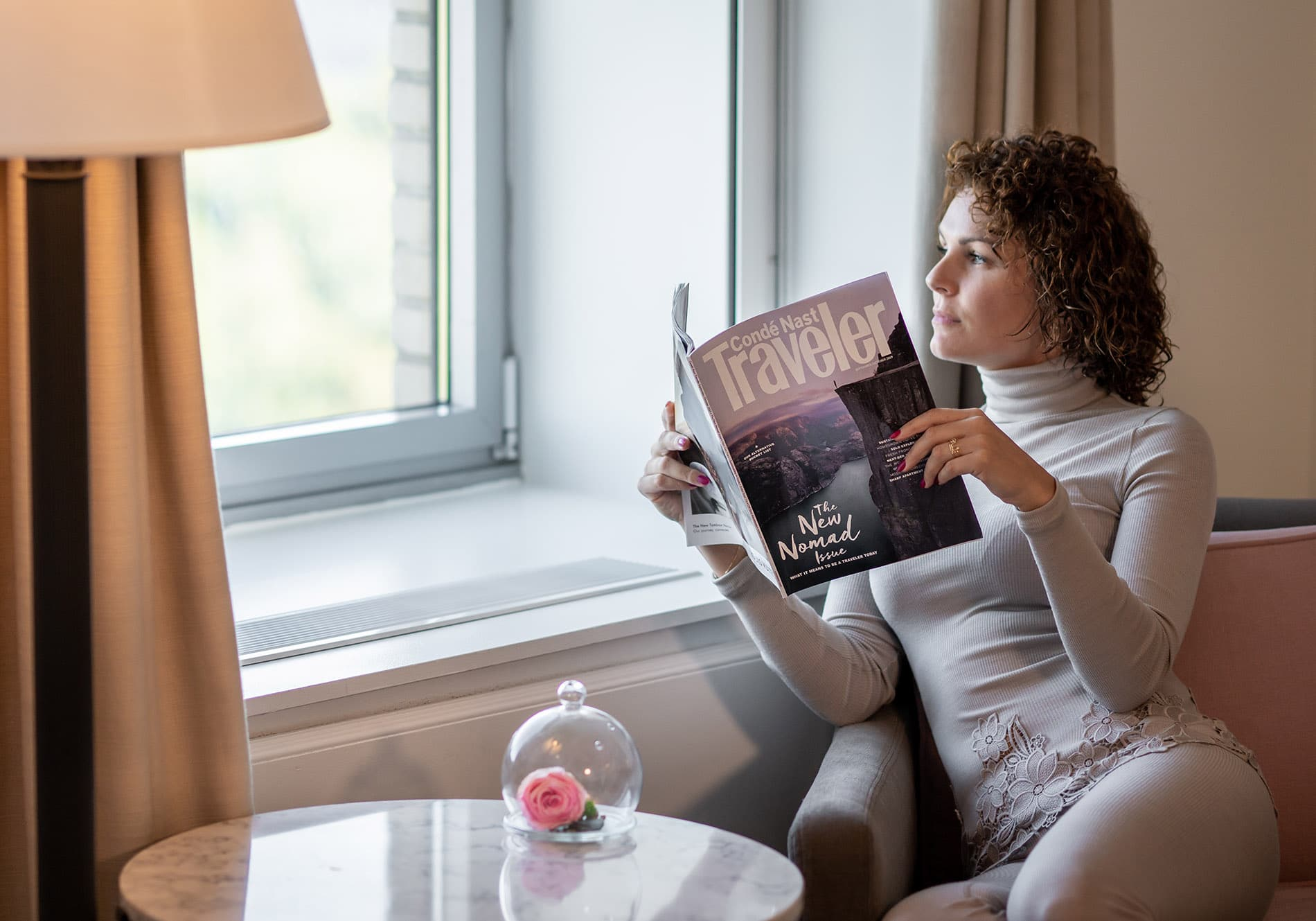 woman in hotel suite reading conde nast magazine