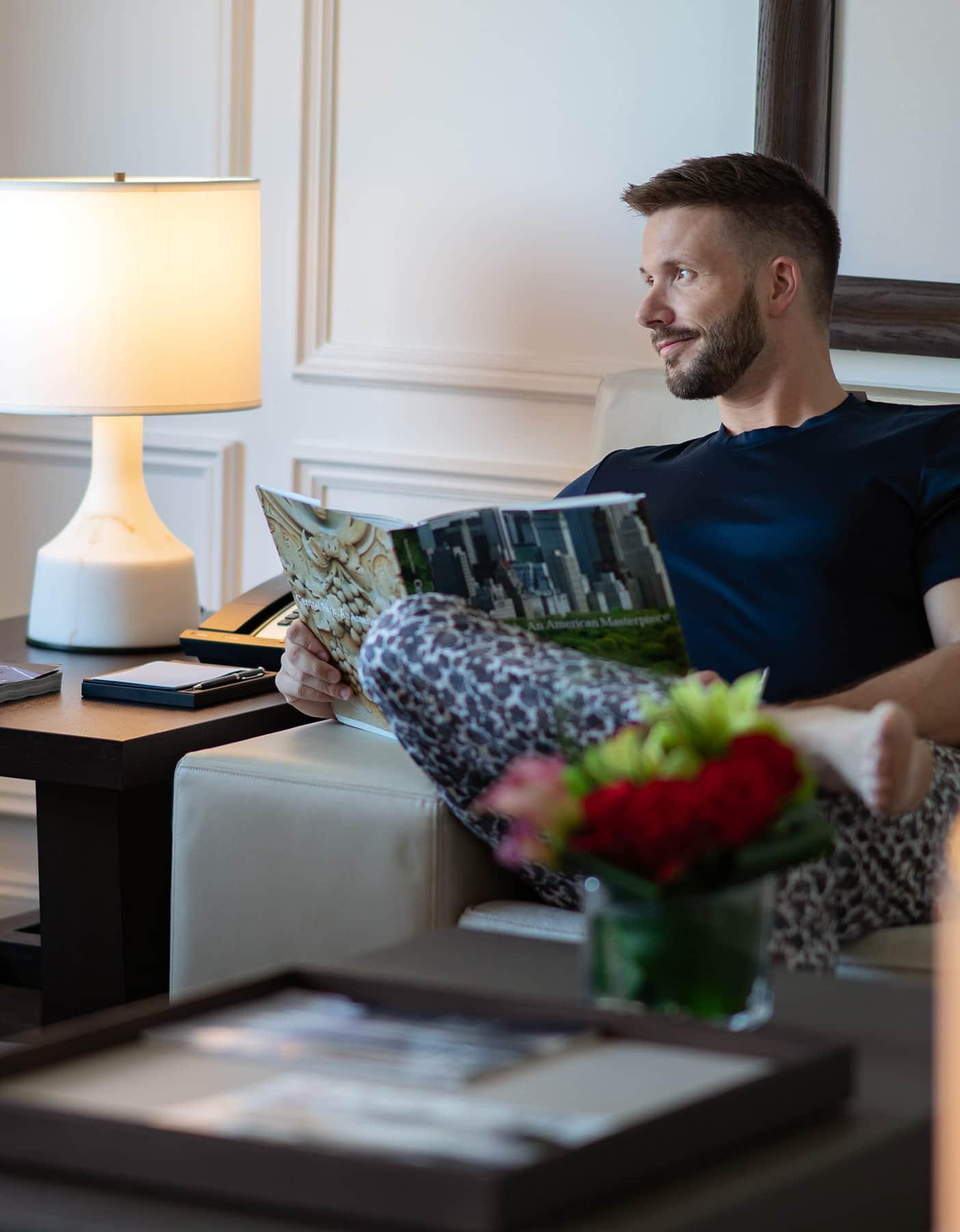 Ritz-Carlton New York Central Park, man in sofa reading magazine