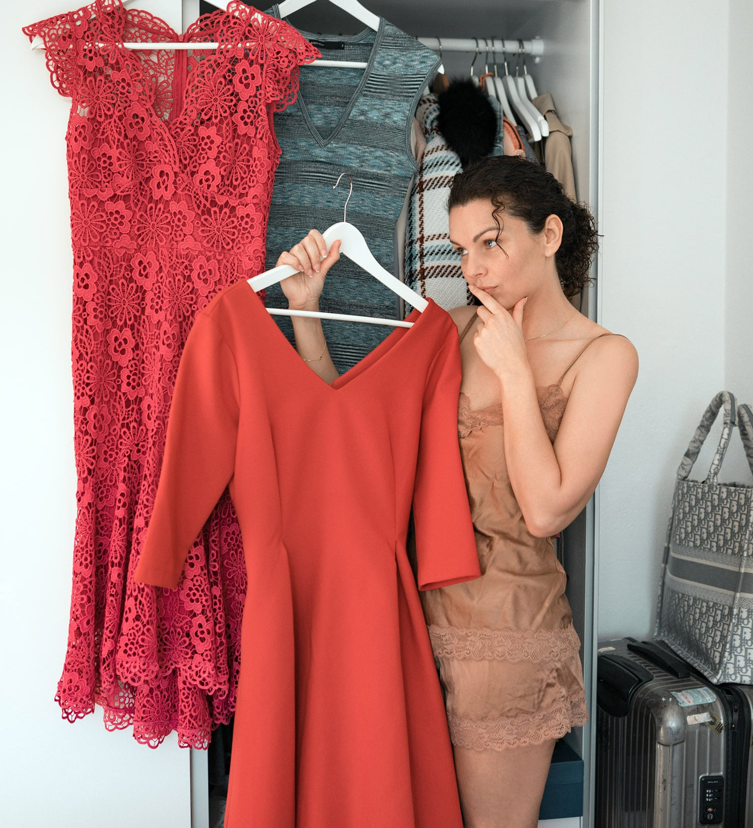 woman holding red dress in front of wardrobe